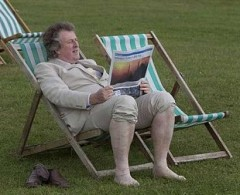 How to dress French but remain defiantly British.  Man wearing linen and no socks sitting in deck chair.