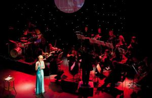 Electric Penelope in blue evening dress singing with the Scottish Romance Orchestra