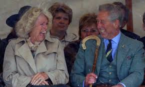 Prince Charles and Camilla laughing at shared currency