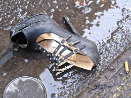 shoe lying in rain drenched gutter